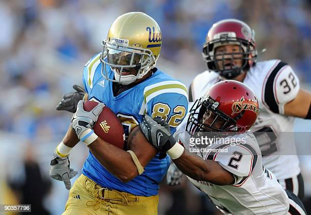 Taylor Embree of the UCLA Bruins carries the ball against Davion Mauldin of the San Diego State Aztecs at the Rose Bowl on September 5 2009 in...