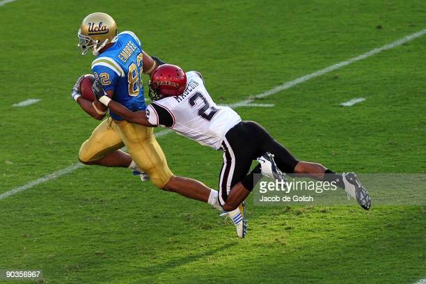 Taylor Embree of the UCLA Bruins runs the ball before getting tackeled by Davion Mauldin of San Diego State at Rose Bowl on September 5 2009 in...