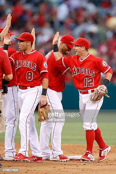Taylor Featherston Albert Pujols and Johnny Giavotella of the Los Angeles Angels of Anaheim celebrate their 42 win over the Seattle Mariners at Angel...