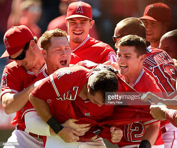 Taylor Featherston of the Los Angeles Angels is mobbed by Kole Calhoun and Johnny Giavotella in response to his run from a wild pitch during the...