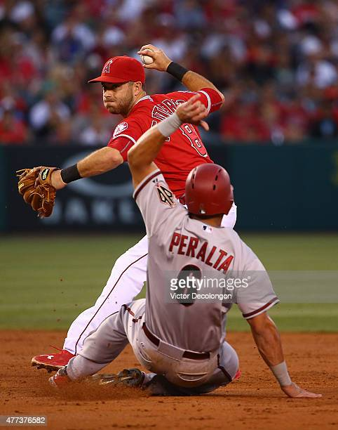 Taylor Featherston of the Los Angeles Angels of Anaheim gets the force out on David Peralta of the Arizona Diamondbacks at second base as Featherston...