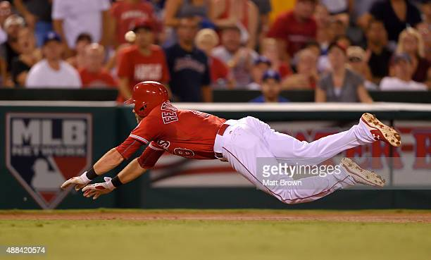 Taylor Featherston of the Los Angeles Angels of Anaheim makes a diving slide into third base for a leadoff triple during the third inning of the game...