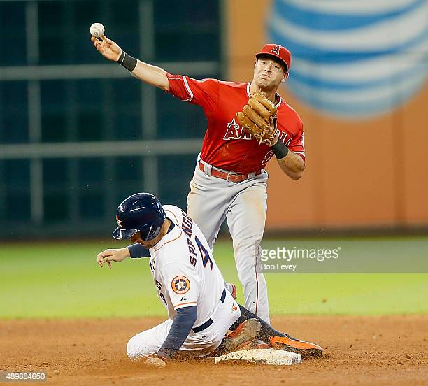 Taylor Featherston of the Los Angeles Angels of Anaheim throws to first base as George Springer of the Houston Astros slides into second base at...