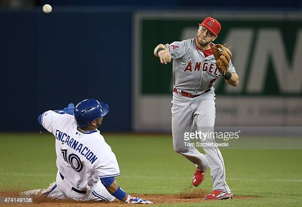 Taylor Featherston of the Los Angeles Angels of Anaheim turns a double play in the fourth inning during MLB game action as Edwin Encarnacion of the...