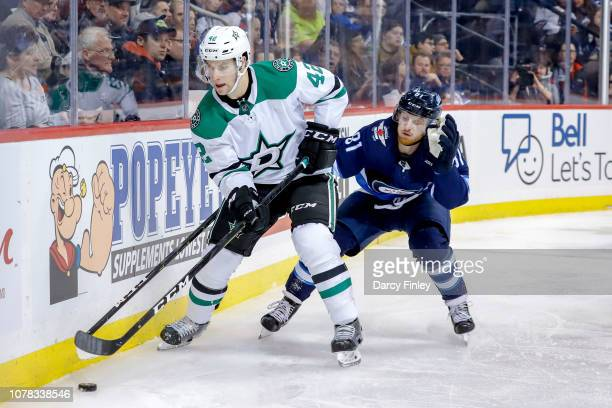 Taylor Fedun of the Dallas Stars plays the puck along the boards as Kyle Connor of the Winnipeg Jets gives chase during second period action at the...