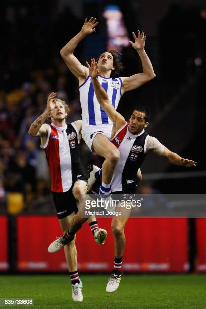 Taylor Garner of the Kangaroos leaps over Shane Savage of the Saints during the round 22 AFL match between the St Kilda Saints and the North...