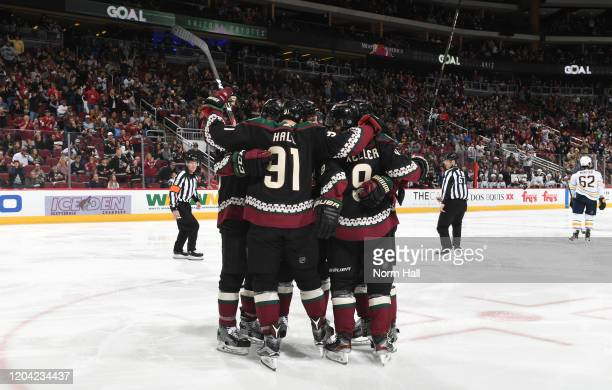 Taylor Hall and Clayton Keller of the Arizona Coyotes celebrate with teammates following a goal against the Buffalo Sabres by teammate Jordan...