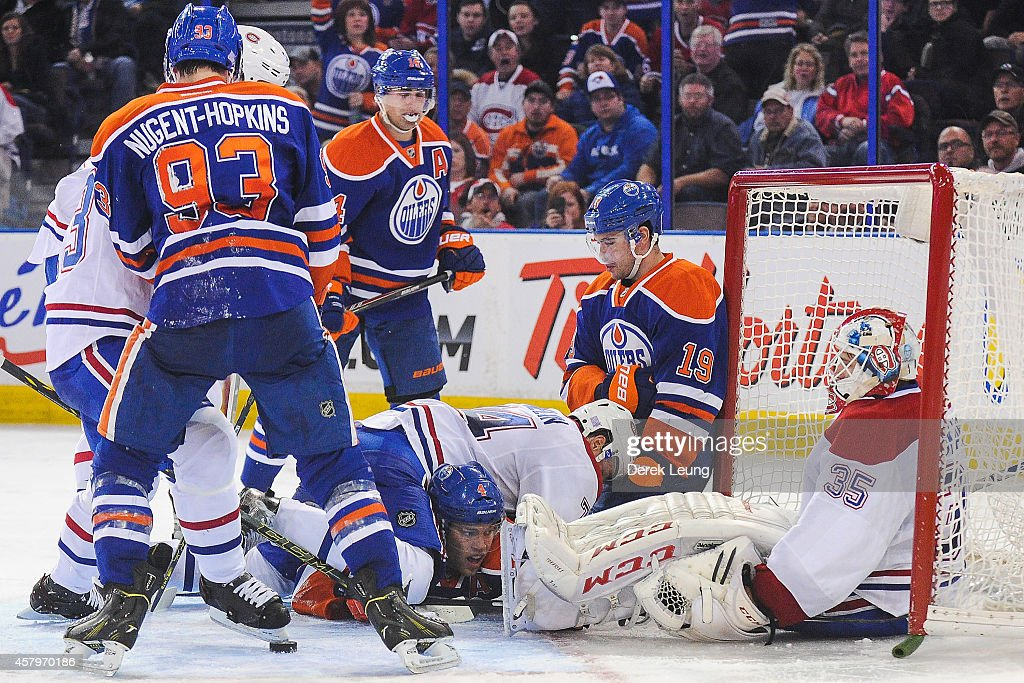 Taylor Hall #4 and goalie Dustin Tokarski #35 of the Edmonton Oilers defend against Alexei Emelin #74 of the Montreal Canadiens after the whistle during an NHL game at Rexall Place on October 27, 2014 in Edmonton, Alberta, Canada. The Oilers defeated the Canadiens 3-0.