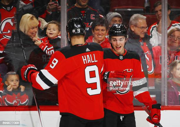 Taylor Hall and Nico Hischier of the New Jersey Devils bump in warmups prior to the game against the Buffalo Sabres at the Prudential Center on...