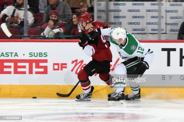 Taylor Hall of the Arizona Coyotes gets tangled with Radek Faksa of the Dallas Stars as he skates for a loose puck during the third period of the NHL...