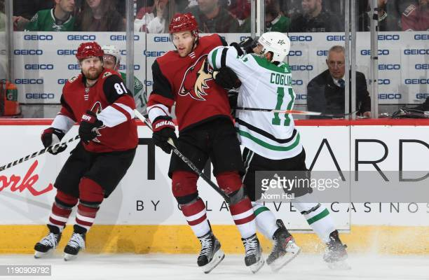 Taylor Hall of the Arizona Coyotes is checked by Andrew Cogliano of the Dallas Stars during the first period of the NHL hockey game at Gila River...