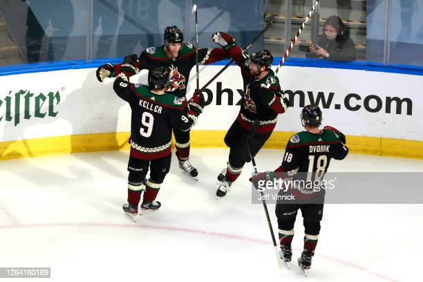 Taylor Hall of the Arizona Coyotes is congratulated by teammates Clayton Keller,Phil Kessel and Christian Dvorak of the Arizona Coyotes after Hall...