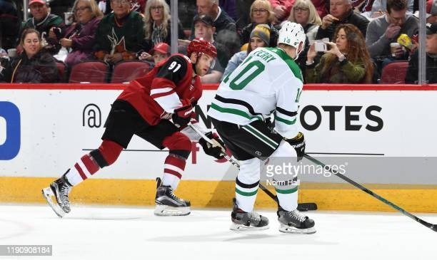 Taylor Hall of the Arizona Coyotes plays the puck along the boards as Corey Perry of the Dallas Stars defends during the first period of the NHL...