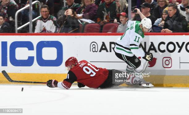 Taylor Hall of the Arizona Coyotes plays the puck away from Andrew Cogliano of the Dallas Stars during the first period of the NHL hockey game at...