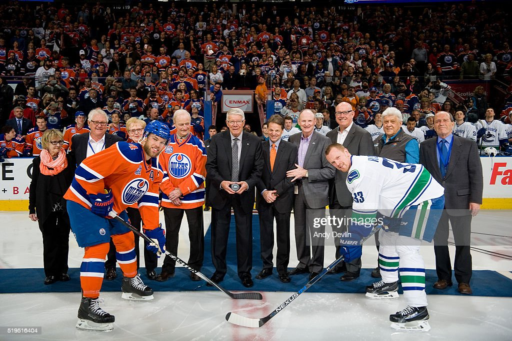 Taylor Hall #4 of the Edmonton Oilers and Henrik Sedin #33 Vancouver Canucks post for the ceremonial puck drop with Brian Ross, Mark Lewis, Sheila McCaskill, Miles Poliak, Rod Phillips, Patrick LaForge, Margaret Mrazek, Barrie Stafford, Val Fonteyne and Cal Nichols on April 6, 2016 at Rexall Place in Edmonton, Alberta, Canada.