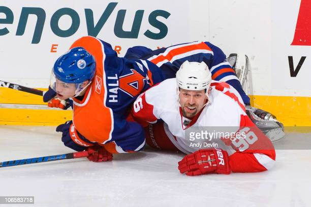 Taylor Hall of the Edmonton Oilers and Tomas Holmstrom of the Detroit Red Wings fall to the ice after colliding at Rexall Place on November 5 2010 in...
