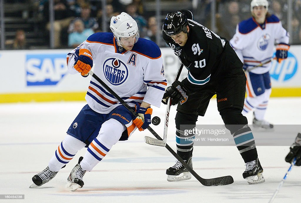 Taylor Hall #4 of the Edmonton Oilers battles for control of the puck with Andrew Desjardins #10 of the San Jose Sharks in the third period at HP Pavilion on January 31, 2013 in San Jose, California.