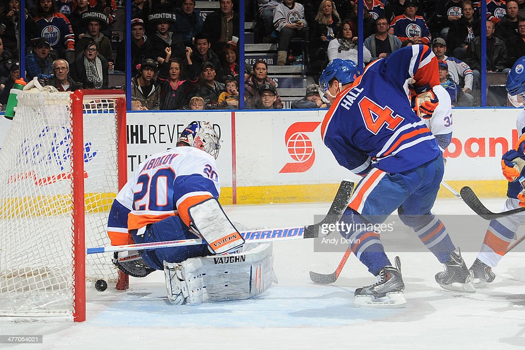 Taylor Hall #4 of the Edmonton Oilers crashes the net as the puck crosses the goal line behind Evgeni Nabokov #20 of the New York Islanders on March 6, 2014 at Rexall Place in Edmonton, Alberta, Canada.