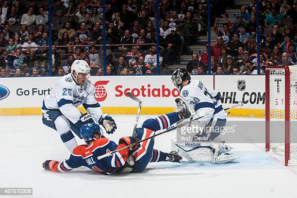Taylor Hall of the Edmonton Oilers is tripped on a break away by Matt Carle of the Tampa Bay Lightning on October 20 2014 at Rexall Place in Edmonton...