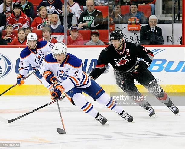 Taylor Hall of the Edmonton Oilers moves the puck against Jordan Staal of the Carolina Hurricanes during their game at PNC Arena on March 16 2014 in...