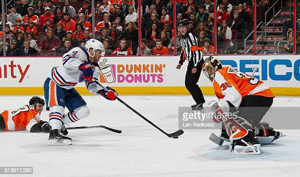 Taylor Hall of the Edmonton Oilers skates past a diving Shayne Gostisbehere of the Philadelphia Flyers to attempt a scoring chance on goaltender...