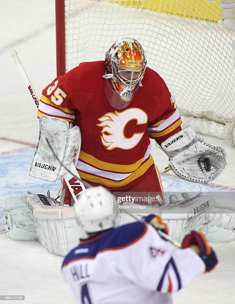 Taylor Hall #4 of the Edmonton Oilers tries to tip the puck past goalie Joey MacDonald #35 of the Calgary Flames at Scotiabank Saddledome on April 3, 2013 in Calgary, Alberta, Canada. Ê