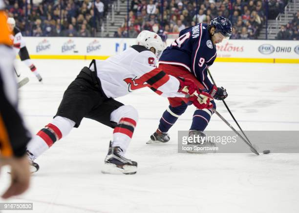 Taylor Hall of the New Jersey Devils and Artemi Panarin of the Columbus Blue Jackets battle for the puck during the second period of the game between...