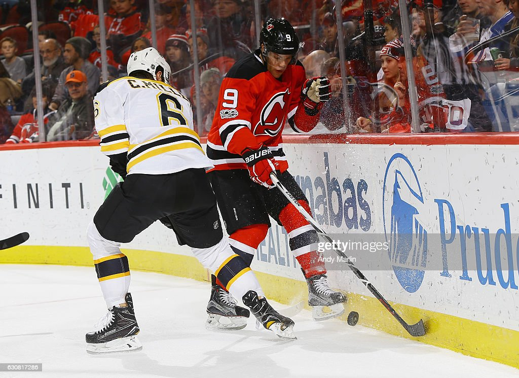 Taylor Hall #9 of the New Jersey Devils and Colin Miller #6 of the Boston Bruins battle for a loose puck during the game at Prudential Center on January 2, 2017 in Newark, New Jersey.