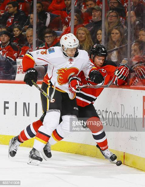 Taylor Hall of the New Jersey Devils and Jyrki Jokipakka of the Calgary Flames battle for a loose puck during the game at Prudential Center on...