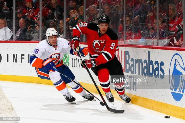 Taylor Hall of the New Jersey Devils and Nikolay Kulemin of the New York Islanders pursue a loose puck during the game at Prudential Center on April...