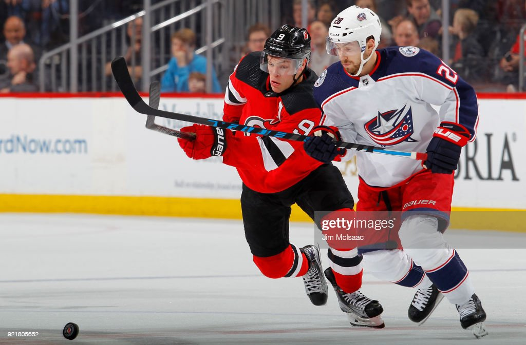 Taylor Hall #9 of the New Jersey Devils battles for the puck against Oliver Bjorkstrand #28 of the Columbus Blue Jackets during the second period on February 20, 2018 at Prudential Center in Newark, New Jersey.