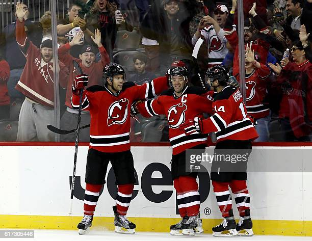 Taylor Hall of the New Jersey Devils celebrates his game winning goal with teammates Andy Greene and Adam Henrique in overtime against Minnesota Wild...
