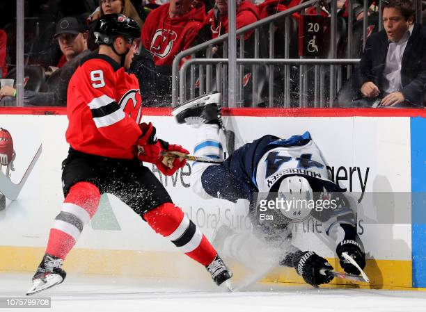 Taylor Hall of the New Jersey Devils checks Josh Morrissey of the Winnipeg Jets in the overtime period at Prudential Center on December 01 2018 in...