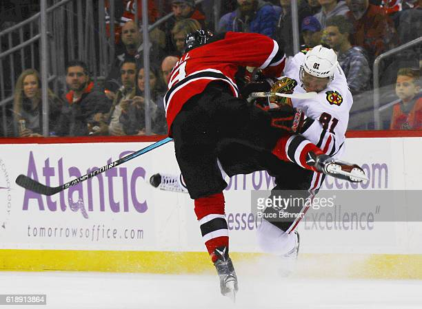 Taylor Hall of the New Jersey Devils checks Marian Hossa of the Chicago Blackhawks during the second period at the Prudential Center on October 28...