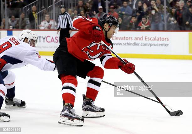 Taylor Hall of the New Jersey Devils heads for the net and scores the game winner as Dmitry Orlov of the Washington Capitals defends in the overtime...