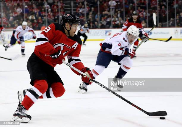 Taylor Hall of the New Jersey Devils heads for the net and scores the game winning goal as Dmitry Orlov of the Washington Capitals defends in the...