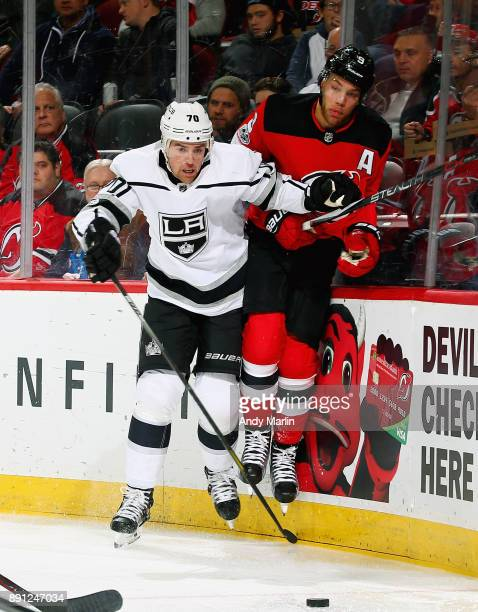 Taylor Hall of the New Jersey Devils is checked into the boards by Tanner Pearson of the Los Angeles Kings during the game at Prudential Center on...