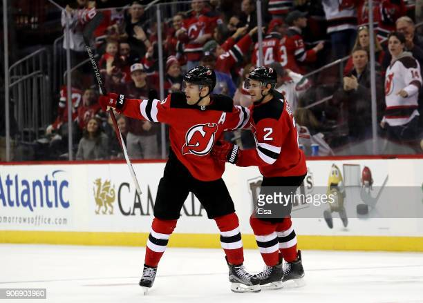 Taylor Hall of the New Jersey Devils is congratulated by teammate John Moore after Hall scored the game winning goal in overtime against the...