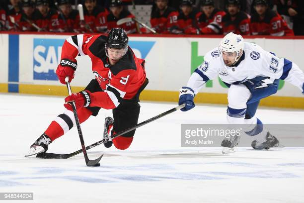 Taylor Hall of the New Jersey Devils plays the puck against Cedric Paquette the Tampa Bay Lightning in Game Four of the Eastern Conference First...