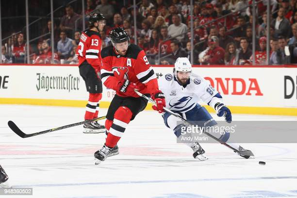 Taylor Hall of the New Jersey Devils skates for the puck against Nikita Kucherov of the Tampa Bay Lightning in Game Four of the Eastern Conference...