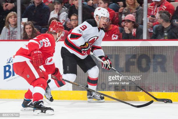 Taylor Hall of the New Jersey Devils skates with the puck along the boards followed by Mike Green of the Detroit Red Wings during an NHL game at Joe...