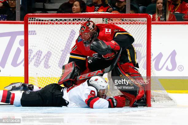 Taylor Hall of the New Jersey Devils slides into Mike Smith of the Calgary Flames during an NHL game on November 5 2017 at the Scotiabank Saddledome...
