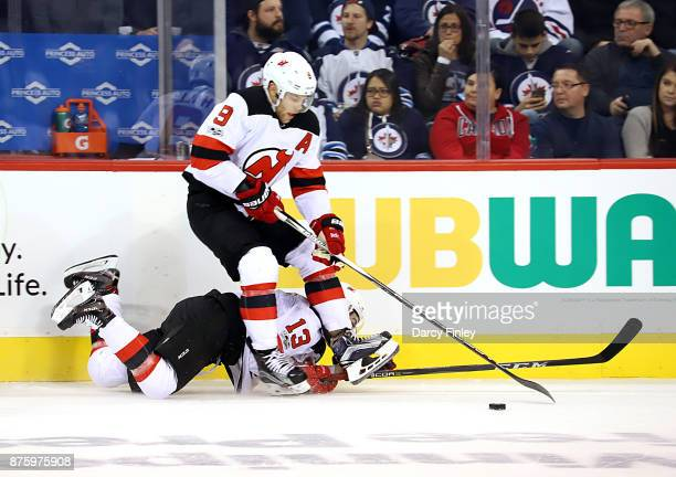 Taylor Hall of the New Jersey Devils trips over teammate Nico Hischier during second period action against the Winnipeg Jets at the Bell MTS Place on...