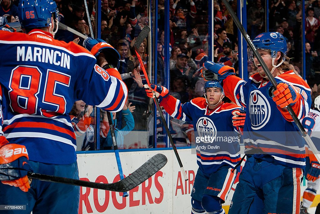 Taylor Hall #4, Philip Larson #46 and Martin Marincin #85 of the Edmonton Oilers celebrate after the game-winning goal in a game against the New York Islanders on March 6, 2014 at Rexall Place in Edmonton, Alberta, Canada.
