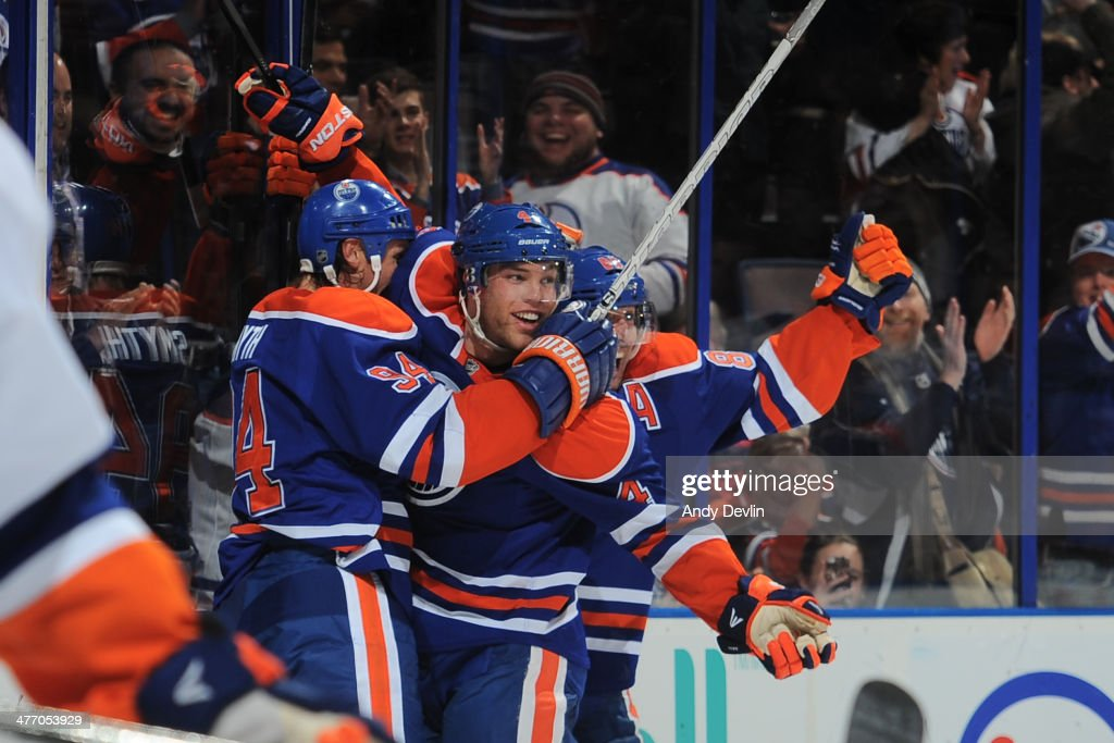 Taylor Hall #4, Ryan Smyth #94 and Sam Gagner #89 of the Edmonton Oilers celebrate after a goal in a game against the New York Islanders on March 6, 2014 at Rexall Place in Edmonton, Alberta, Canada.