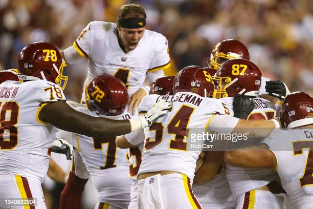Taylor Heinicke and the Washington Football Team celebrate a 30-29 win over the New York Giants at FedExField on September 16, 2021 in Landover,...