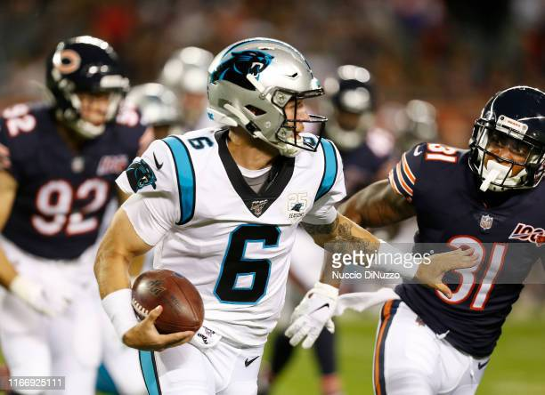 Taylor Heinicke of the Carolina Panthers carries the ball against Jonathon Mincy of the Chicago Bears during the second half of a preseason at...