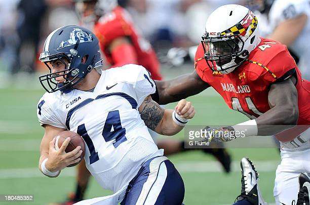 Taylor Heinicke of the Old Dominion Monarchs is tackled by Marcus Whitfield of the Maryland Terrapins at Byrd Stadium on September 7 2013 in College...