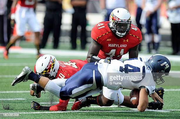 Taylor Heinicke of the Old Dominion Monarchs is tackled by Marcus Whitfield and Matt Robinson of the Maryland Terrapins at Byrd Stadium on September...