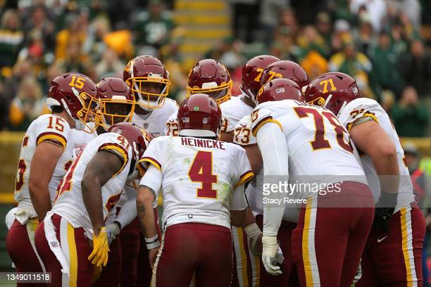Taylor Heinicke of the Washington Football Team calls a play in the huddle during a game against the Green Bay Packers at Lambeau Field on October...